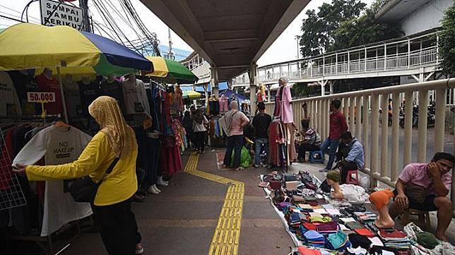 Warga berbagi jalan dengan PKL yang berjualan di kolong trotoar jembatan penyebrangan multiguna (skybridge) Tanah Abang, Jakarta, Rabu, 15 Mei /2019 Suasana penataan kawasan Tanah Abang yang tidak maksimal serta tidak terakomodirnya PKLmenyebabkan mereka kembali berjualan di trotoar untuk mencari rezeki di bulan Ramadhan. ANTARA/Indrianto Eko Suwarso