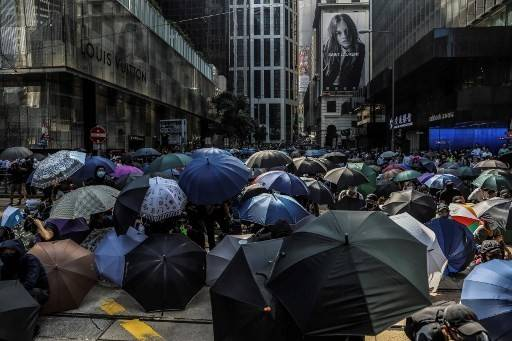 Demonstrators shield beneath umbrellas as police arrive during a flash mob protest in the Central district in Hong Kong on November 13, 2019. Pro-democracy protesters stepped up on November 13 a