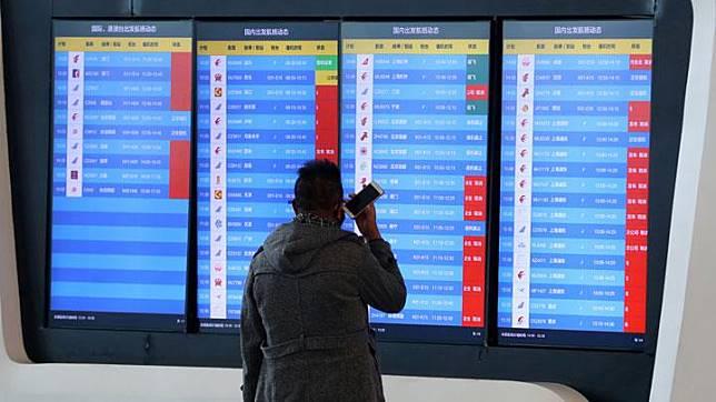 Seorang pria melihat sejumlah jadwal pesawat yang dibatalkan sebuah bandara di Wuhan, Provinsi Hubei, Cina, 23 Januari 2020. Beberapa maskapai memilih membatalkan sejumlah jadwal penerbangan dari dan ke Wuhan sebagai antisipasi merespons pemberitahuan larangan perjalanan dari otoritas Wuhan mengenai dampak wabah Virus Corona. cnsphoto via REUTERS