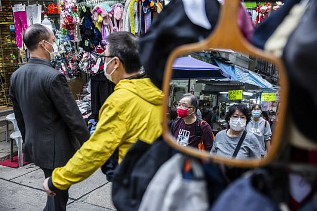 People wearing protective face masks walk through a market in the wan chai district of Hong Kong on Feb. 25, 2020.