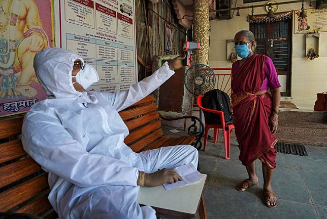 Sanjay Meriya, 30, also known as the Spindoctor, wearing a protective gear checks temperature of a woman in a temporary health center where he coaches slum dwellers on the precautions they should take to avoid being infected with the COVID-19, in Mumbai, India May 25, 2020. Picture taken on Monday.