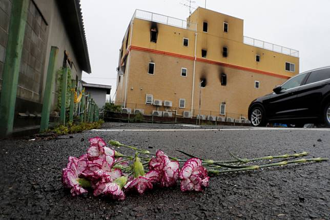 Flowers are placed in front of the torched Kyoto Animation building in respect for the victims, in Kyoto, Japan, July 19, 2019.