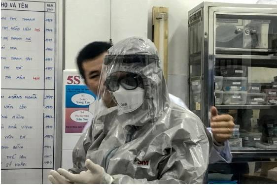 Wakil Menteri Kesehatan Vietnam, Nguyen Truong Son, mengenakan pakaian pelindung sebelum memasuki area isolasi dan mengunjungi dua pasien yang positif terinfeksi virus corona di Rumah Sakit Cho Ray, Ho Chi MInh City, pada 23 Januari 2020.(AFP/BACH DUONG)  Artikel ini telah tayang di Kompas.com dengan judul