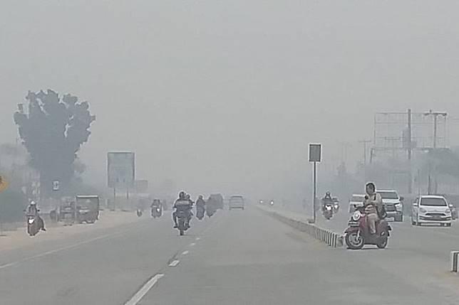Kabut asap makin pekat di Pekanbaru, Riau, dengan jarang pandang sekitar 300 meter, Jumat (13/9/2019).(KOMPAS.COM/IDON)