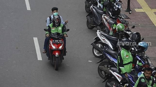 Sebagai ilustrasi PSBB Jakarta: Ojek online membawa penumpang melintas di kawasan Palmerah, Jakarta, Selasa (7/4).  [Suara.com/Angga Budhiyanto]