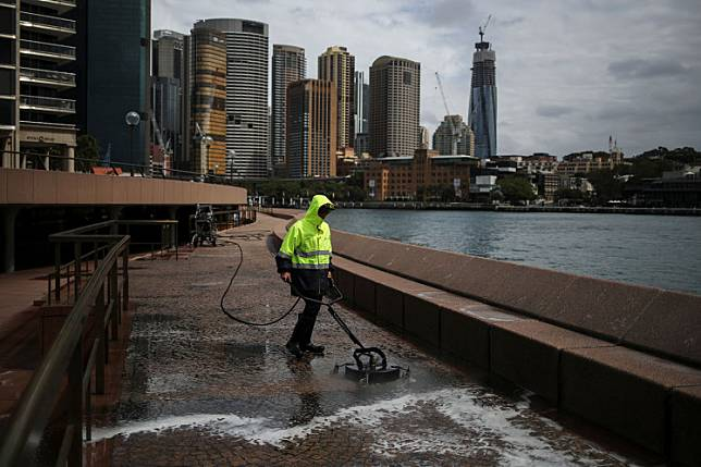 A worker cleans the mostly deserted waterfront area of the Sydney Opera House, in the wake of New South Wales implementing measures shutting down non-essential businesses and moving toward harsh penalties to enforce self-isolation as the spread of coronavirus disease (COVID-19) reached what the state's premier calls a