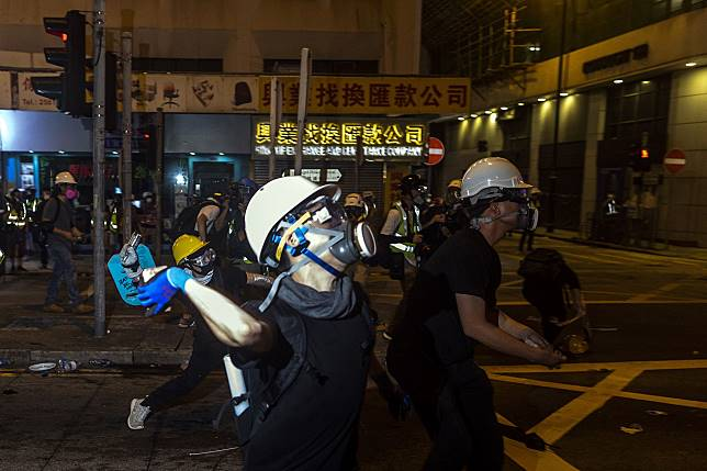 Demonstrators throw projectiles towards riot police during a stand off at a protest in the Sheung Wan district of Hong Kong, China, on Sunday, July 21, 2019. Photographer: Justin Chin/Bloomberg