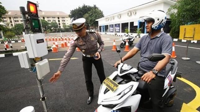 Kepala Seksi SIM Subdit Regident Ditlantas Polda Metro Jaya AKP Lalu Hedwin (kiri) menjelaskan cara mengikuti uji praktik SIM sistem elektronik di Satuan Penyelenggara Administrasi (Satpas) SIM Daan Mogot, Jakarta, Selasa (10/12/2019) [ANTARA FOTO/Rivan Awal Lingga/pd].