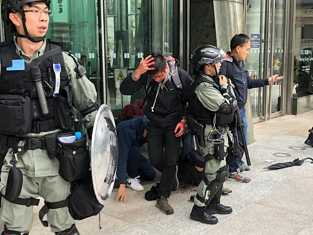 Hong Kong protests: two plain-clothes police officers beaten, tear gas fired and rally organiser arrested as mayhem breaks out in Central