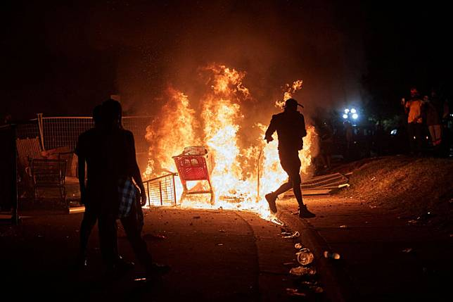 Protesters gather to watch shopping carts burning near the Minneapolis Police third precinct after a white police officer was caught on a bystander's video pressing his knee into the neck of African-American man George Floyd, who later died at a hospital, in Minneapolis, Minnesota, US, May 27, 2020.