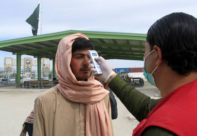 A health worker takes the temperature of a man, who returned from Afghanistan, for a medical observation as a preventive measure following the coronavirus outbreak, outside a medical camp set up near the Friendship Gate, crossing point at the Pakistan-Afghanistan border town of Chaman, Pakistan Feb. 26. Pakistan has detected its first two cases of novel coronavirus