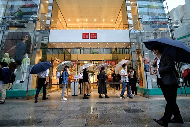 Customers wait in a queue outside a Uniqlo store selling face masks made by Japan's Fast Retailing Co. in Tokyo's Ginza shopping district on June 19, 2020.