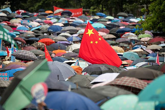 A Chinese flag flies above demonstrators during the pro-government rally. Photographer: David Paul Morris/Bloomberg