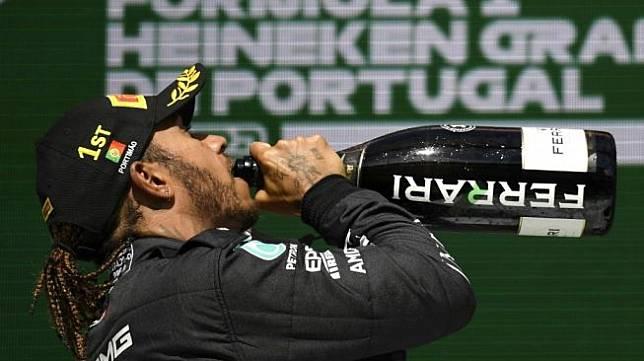 Selebrasi Lewis Hamilton usai memenangi F1 GP Portugal 2021. [GABRIEL BOUYS / POOL / AFP]