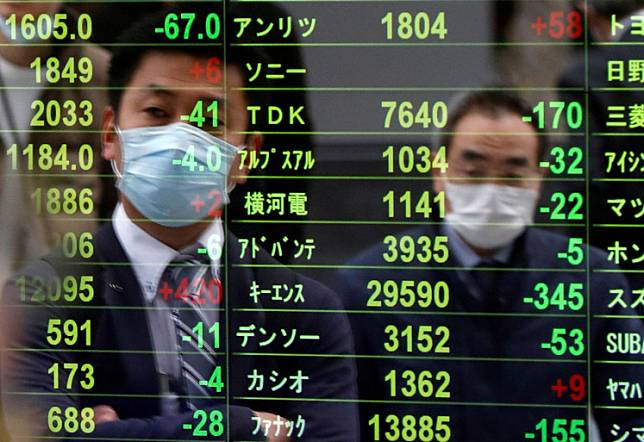 Passersby wearing protective face masks following an outbreak of the coronavirus disease (COVID-19) are reflected on a screen displaying stock prices outside a brokerage in Tokyo, Japan, March 17, 2020.