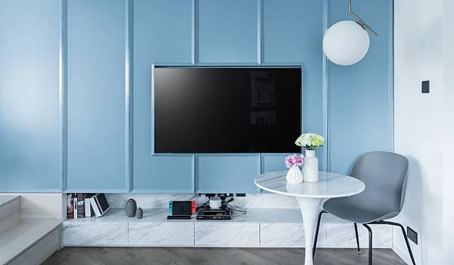 灰藍色歐式花線主題牆是全屋焦點,其身兼電視櫃及衣櫃一職,把衣物、雜物巧妙地隱藏於櫃內。(受訪者提供)