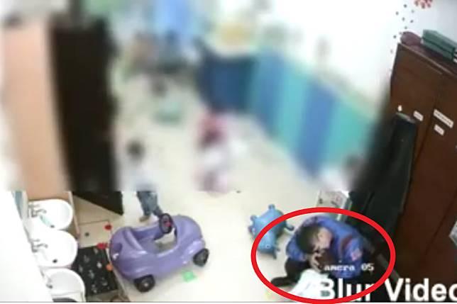 從涉嫌虐童的托嬰中心監視器畫面看到,一位男姓職員雙手捧起一名幼童,做出疑似親吻的動作