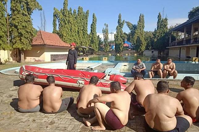 Police officers listen to their instructor during a weight-loss program at the State Police Academy in Mojokerto, East Java, on Thursday.