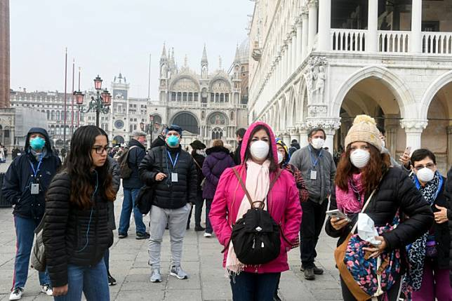 Tourists wearing protective masks visit Venice on February 25, 2020, during the usual period of the Carnival festivities which have been cancelled following an outbreak of the COVID-19 novel coronavirus in northern Italy. - Italy's new coronavirus spread south on February 25 to Tuscany and Sicily, as the civil protection agency reported a surge in the number of infected people and Rome convened emergency talks.