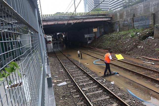 Disrupted operations: A railway officer gives a signal using his flag on flooded tracks at Sudirman Station in Jakarta on Tuesday.