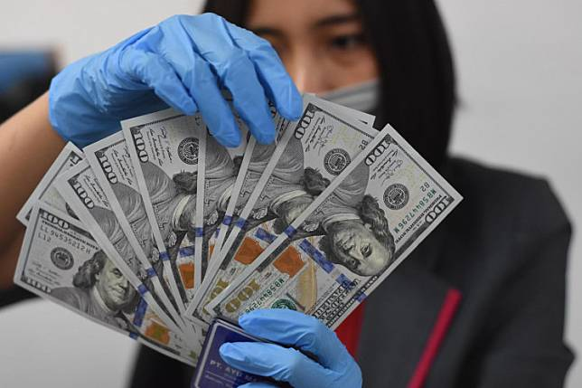 An officer is arranging US dollars in one of the foreign currency exchange outlets in Jakarta, on Thursday March 19. 2020.A resurgent coronavirus pandemic in the United States and the prospect of improving growth abroad are souring some investors on the dollar, threatening a years-long rally in the currency.