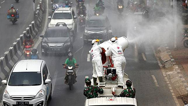 Indonesia's Red Cross personnel wearing protective suits spray disinfectant on the road to prevent the spread of the coronavirus disease (COVID-19) in Jakarta, Indonesia, March 28, 2020. Twelve more people had died from the virus, bringing the death toll to 144, Achmad Yurianto, the official, said. Sixty-four people had recovered, he added. Yurianto added that the country had tested more than 6,500 people across the country. REUTERS/Ajeng Dinar Ulfiana