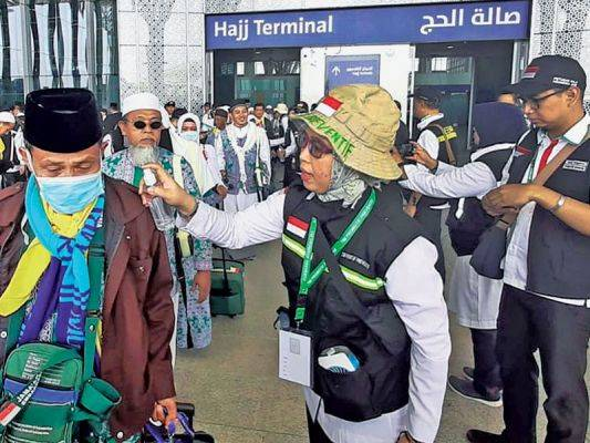 Petugas menyemprotkan air ke jemaah haji kloter pertama yang baru mendarat di Bandara Internasional Amir Muhammad bin Abdul Aziz, Madinah.