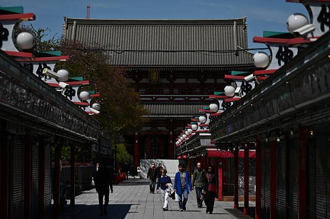 People walk past closed shops outside the Senso-ji temple in Tokyo's Asakusa area on April 10, 2020.