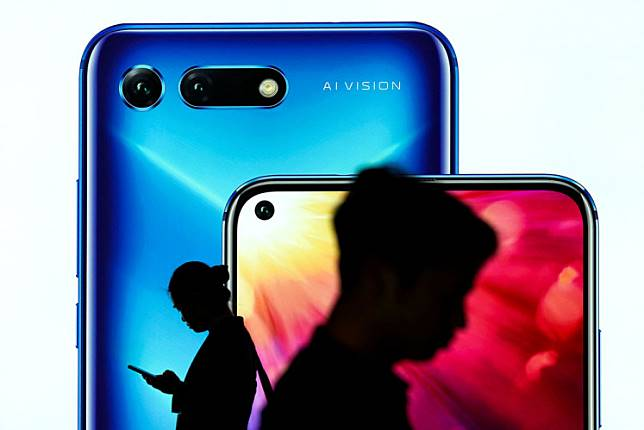 People walk past an advertisement for Huawei's Honor smartphones at an airport in Shenzhen, Guangdong province, China, on Feb. 27. The United States has temporarily eased trade restrictions on China's Huawei to minimize disruption for its customers.
