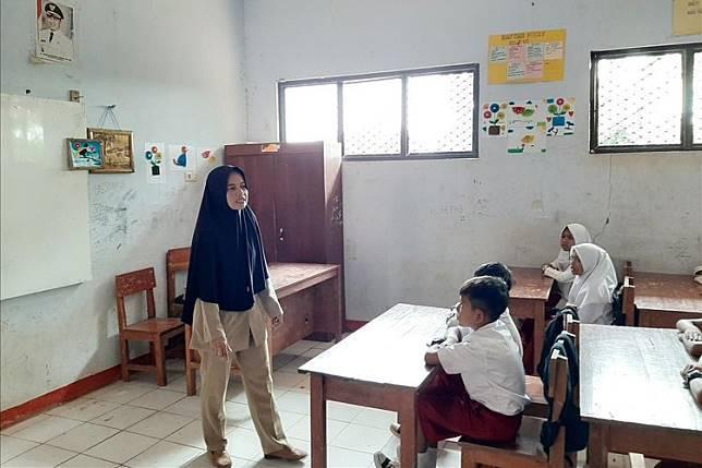 Nining Suryani (44) menunjukkan isi rumahnya yang menempati bagian toilet sekolah di SDN Karyabuana 3, Kecamatan Cigeulis, Kabupaten Pandeglang, Banten, Senin (15/7/2019) | KOMPAS.com/ ACEP NAZMUDIN