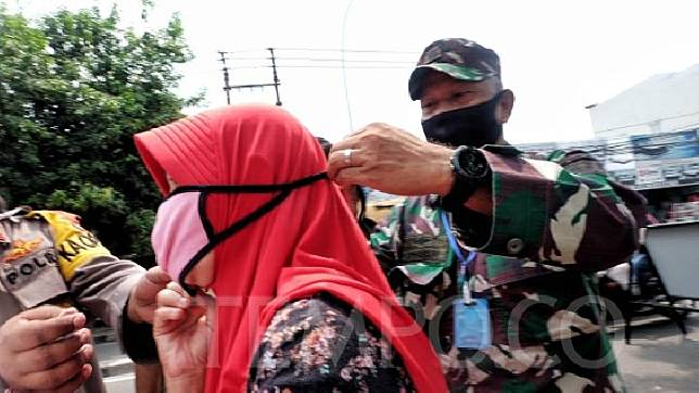 A soldier helps a resident wear a face mask during an inspection of the large-scale social restrictions (PSBB) policy on Jl. HOS Cokroaminoto, Larangan, Tangerang, Banten, Saturday, April 18, 2020. TEMPO / Hilman Fathurrahman W