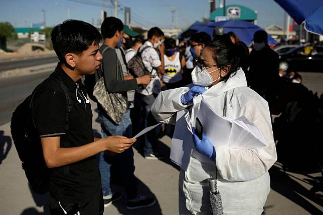 Personnel of an assembly factory, in protective gear, talk to job seekers as the COVID-19 outbreak continues in Ciudad Juarez, Mexico June 17, 2020. Mexico on Wednesday posted a fresh record for new coronavirus cases reported on a single day, with 6,995 infections, overtaking Spain to register the world's eighth highest case count, according to a Reuters tally.