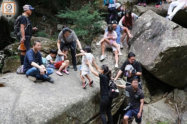 不少父母罔顧安全,帶同年幼子女攀上照鏡潭岩石。