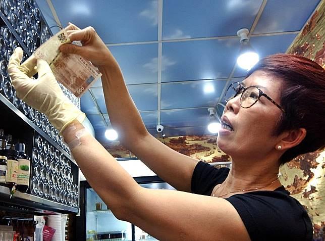 陳小姐示範留意500元紙鈔的水印及金屬线。
