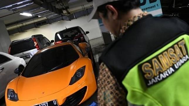 Petugas Samsat Jakarta Utara mengecek pajak sebuah mobil mewah saat razia supervisi pencegahan pajak mobil mewah di Apartemen Regatta, Jakarta Utara di Jakarta, Kamis (5/12/2019) [ANTARA FOTO/M Risyal Hidayat/wsj]