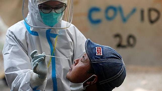 A healthcare worker in protective gear collects a swab sample to be tested for the coronavirus disease (COVID-19) from a man at a traditional textile market in Jakarta, Indonesia, July 2, 2020. Indonesia reported 1,624 coronavirus infections on Thursday in its biggest jump in new cases since the epidemic began, health ministry official Achmad Yurianto said. This brings the total number of infections to 59,394. REUTERS/Willy Kurniawan