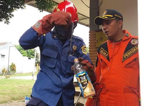 Petugas memasukkan ular kobra ke botol, Minggu 8 Desember 2019. Ular tersebut meneror warga di kompleks perumahaan Royal Citayam Residence, Bojong Gede. TEMPO/M.A MURTADHO