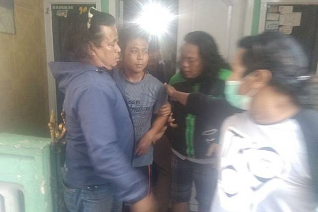 Police arrest 25-year-old Sidiq Nugraha ('second left') who allegedly threw his semen at several women in Tasikmalaya, West Java, in a raid at his relative's house on Monday.