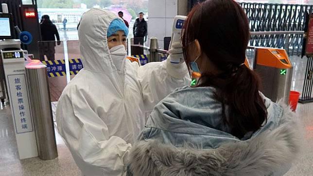 Pekerja memeriksa suhu penumpang yang tiba di Stasiun Xianning Utara pada malam perayaan Tahun Baru Imlek China, di Xianning, kota yang berbatasan dengan Wuhan di provinsi Hubei, Cina 24 Januari 2020. REUTERS/Martin Pollard