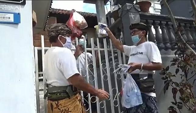 Warga Kota Denpasar menjalankan isolasi mandiri di rumah mendapat bantuan makanan dan snack.(Foto: iNews/Indira Arri)