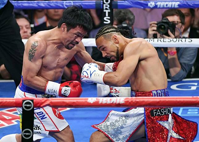 Manny Pacquiao (L) and Keith Thurman battle in the first round of their WBA welterweight title fight at MGM Grand Garden Arena on July 20, 2019 in Las Vegas, Nevada. Pacquiao won in a split decision.