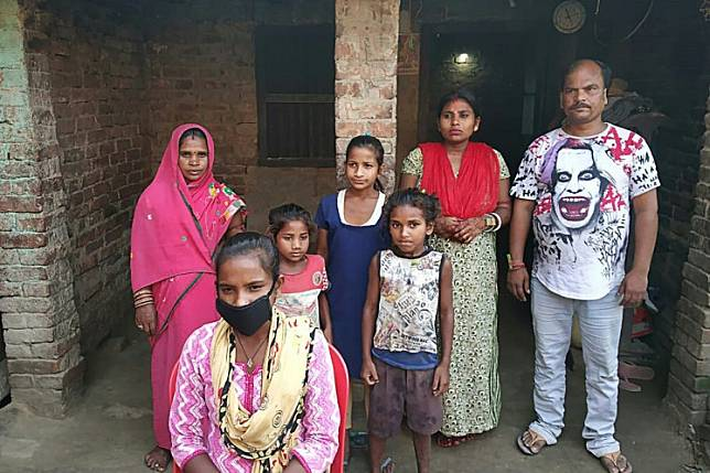 Jyoti Kumari Paswan (center-bottom) and her family stand in front of their house in Siruhully village at Darbhanga district, on May 23. A 15-year-old girl who cycled her ailing father 1,200 kilometers across India during a nationwide coronavirus lockdown has been offered a chance to break into the national cycling team.
