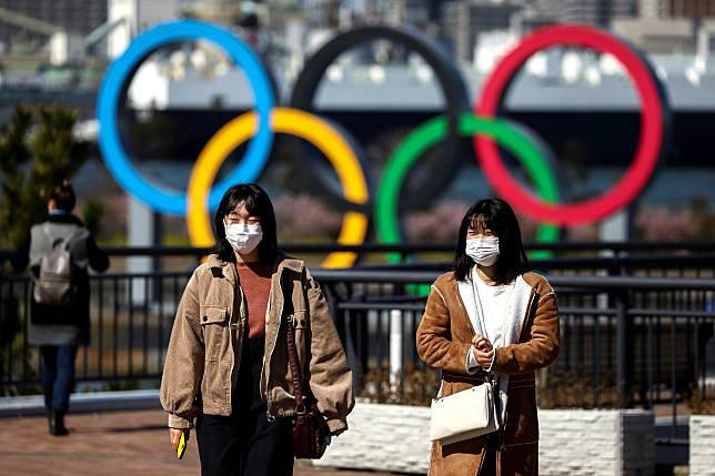 People wearing protective face masks are seen in front of the Giant Olympic rings at the waterfront area at Odaiba Marine Park in Tokyo