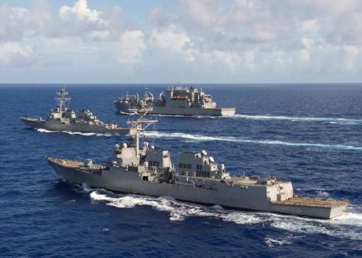 """This US Navy photo obtained October 28, 2016 shows The guided-missile destroyers USS Spruance (DDG 111), front, and USS Decatur (DDG 73) and the Military Sealift Command fleet oiler USNS Carl Brashear (T-AO 7) as they steam in formation in the Pacific Ocean following a joint exercise with the US Air Force 34th Expeditionary Bomb Squadron from Anderson Air Force Base, Guam,on October 27, 2016. Spruance and Decatur and the guided-missile destroyer USS Momsen (DDG 92), along with embarked """"Warbirds"""" and """"Devilfish"""" detachments of Helicopter Maritime Strike Squadron (HSM) 49, are deployed in support of maritime security and stability in the Indo-Asia-Pacific as part of a US 3rd Fleet Pacific Surface Action Group (PAC SAG) under Commander, Destroyer Squadron (CDS) 31."""
