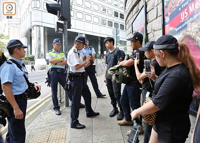 有數名穿着黑衣人士在律政中心側門停留,被警員截查。(李志湧攝)