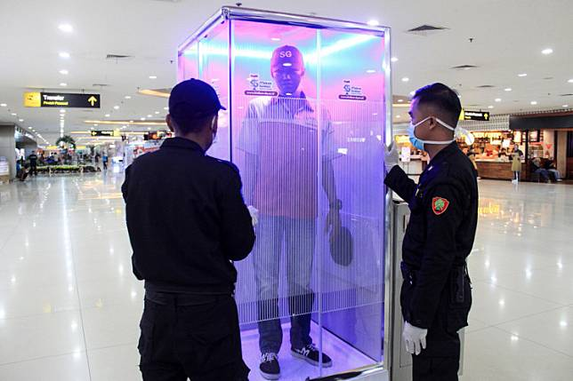 A passenger uses the disinfection chamber installed at Terminal 2 of Juanda International Airport in Sidoarjo, East Java, on March 22.