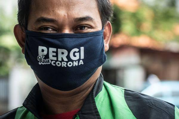 Pengemudi ojek daring menggunakan masker.