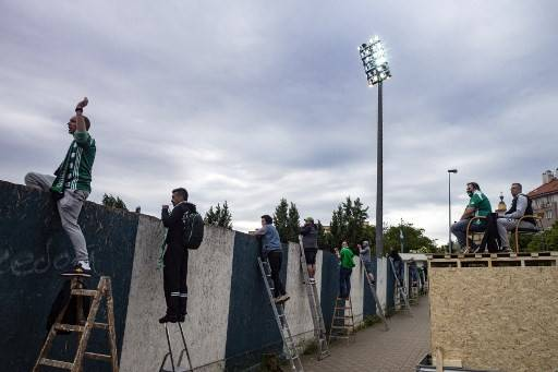 Bohemians' supporters watch the Czech First League (aka Fortuna liga) football match between Bohemians 1905 and SK Dynamo Ceske Budejovice behind a wall amid the new coronavirus restrictions on Sunday in Prague.The Czech government on Monday decided to allow Czechs to travel to most European countries from June 15 without submitting a negative COVID-19 test upon return.