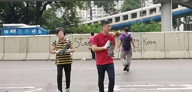 何啟明(紅衣)同義工落區搬番啲磚同雜物返上行人路。(互聯網)