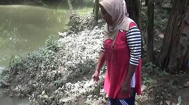 Partini menunjukkan lokasi tetangganya Suwarni diterkam buaya saat mencuci di Sungai Way Kunyit, Pekon Banjar Sari, Kabupaten Tanggamus, Lampung, Senin (30/3/2020). (Foto: iNews/ Indra Siregar)